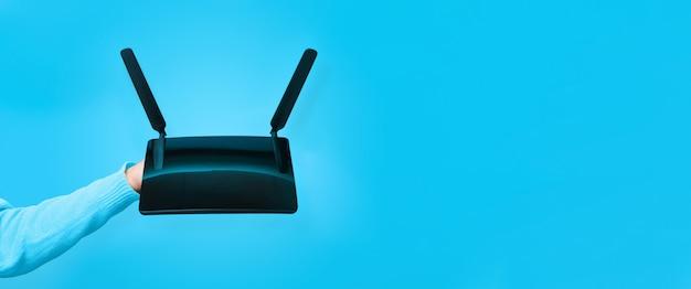 Czarny router wifi pod ręką na niebieskim