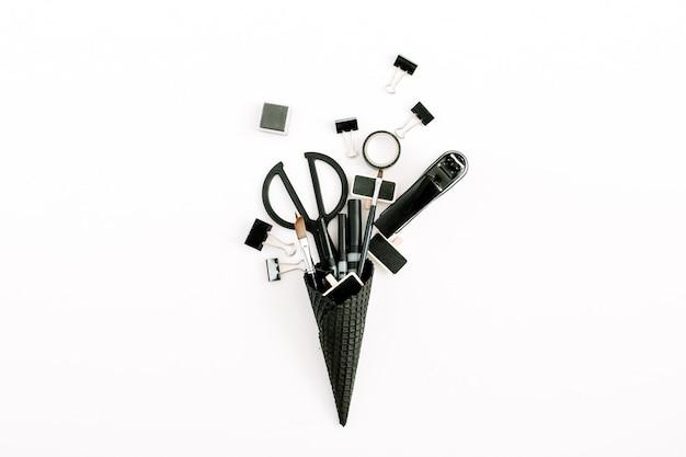 Czarny rożek waflowy z narzędziami biurowymi.