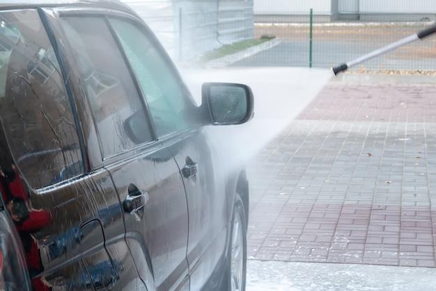 Czarny samochód myje się silnym strumieniem wody na myjni samoobsługowej