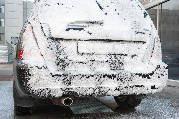 Czarny samochód pokryty pianką na myjni samoobsługowej. widok z tyłu