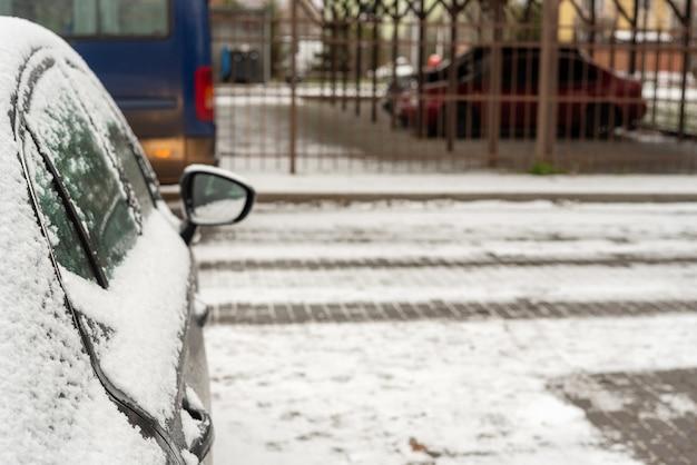 Czarny samochód pokryty śniegiem na parkingu. widok z tyłu.