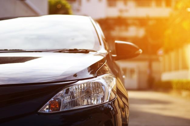 Czarny samochód reflektory na rogu ulicy z promieni słonecznych