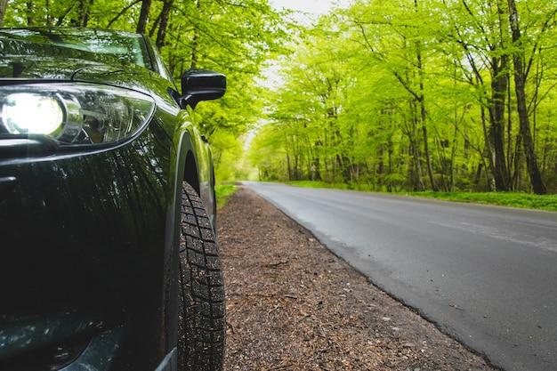 Czarny Samochód Stoi Na Poboczu Leśnej Drogi Premium Zdjęcia