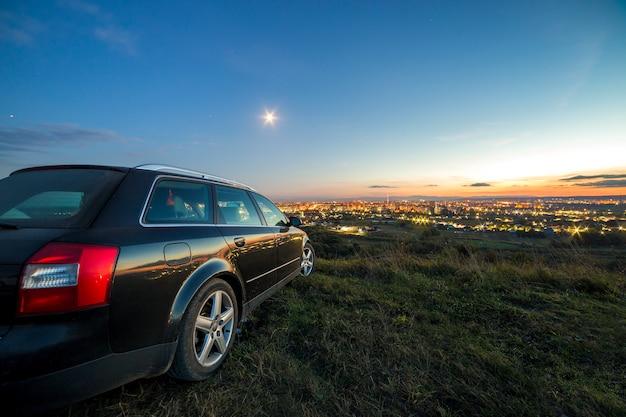 Czarny samochód zaparkowany w nocy na zielonych łąkach z odległymi budynkami miasta i jasnym błękitnym niebem.