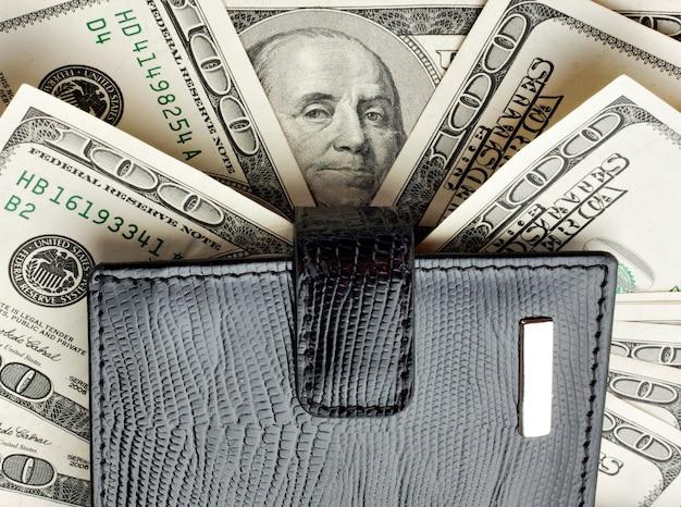 Czarny skórzany portfel na stercie pieniędzy