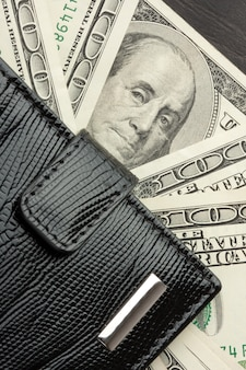Czarny skórzany portfel pełen pieniędzy