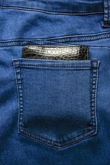 Czarny skórzany portfel w tylnej kieszeni dżinsów o fakturze denimu.