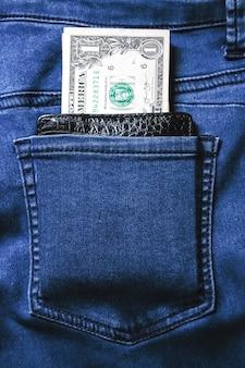Czarny skórzany portfel z pieniędzmi w tylnej kieszeni dżinsów o fakturze denimu.