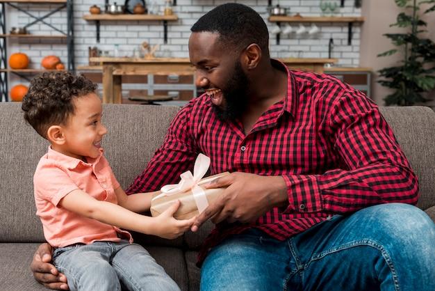 Czarny śliczny syn daje prezentowi ojciec