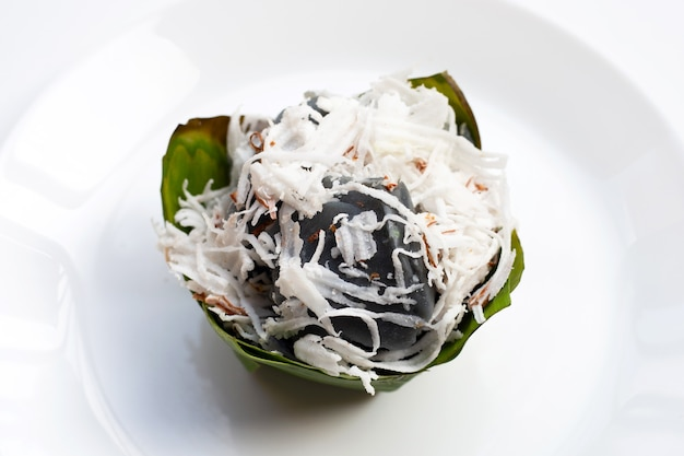 Czarny słodki budyń kokosowy z polewą kokosową w liściach bananowca na białym tle
