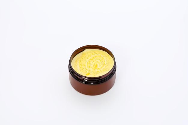 Czarny słoik z żółtym kremem z olejem z rokitnika na białym tle.