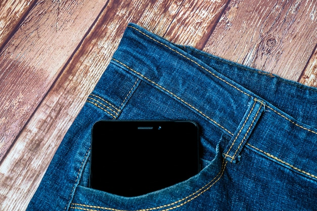Czarny smartfon wystaje z kieszeni dżinsów