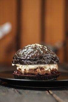 Czarny soczysty burger na drewnianym stole ciemny talerz