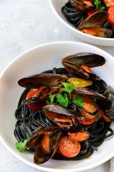 Czarny spaghetti jedzenie flay tay. czarny makaron z owocami morza z małżami.