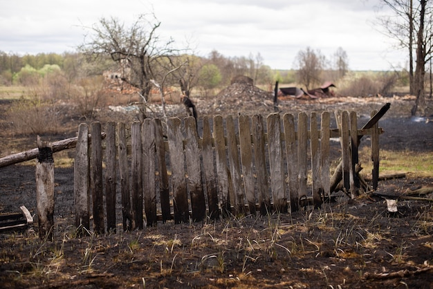 Czarny spalony drewniany płot, dużo zniszczonych śmieci