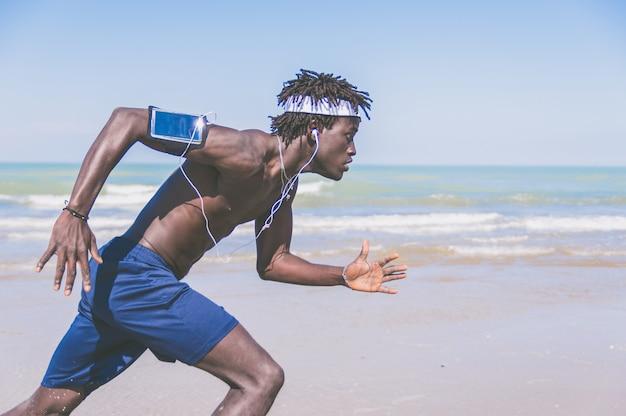 Czarny sportowiec uciekinier - mężczyzna biegacz na plaży, słuchanie muzyki na smartfonie. trening jogger z opaską na inteligentny telefon,