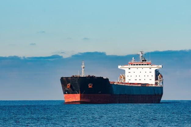 Czarny statek towarowy poruszający się po wodach morza bałtyckiego. ryga, europa