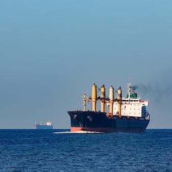 Czarny statek towarowy wypływający z morza bałtyckiego