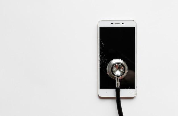 Czarny stetoskop na łamanym mobilnym smartphone po kropli, widok od above, na białym tle. skopiuj miejsce