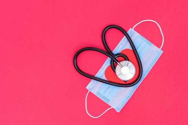 Czarny stetoskop w kształcie serca z medyczną maską ochronną w kolorze jasnoróżowym