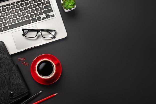 Czarny stół biurowy z pustego ekranu laptopa, notebooka, filiżankę kawy i inne biuro. widok z góry z miejsca na kopię.