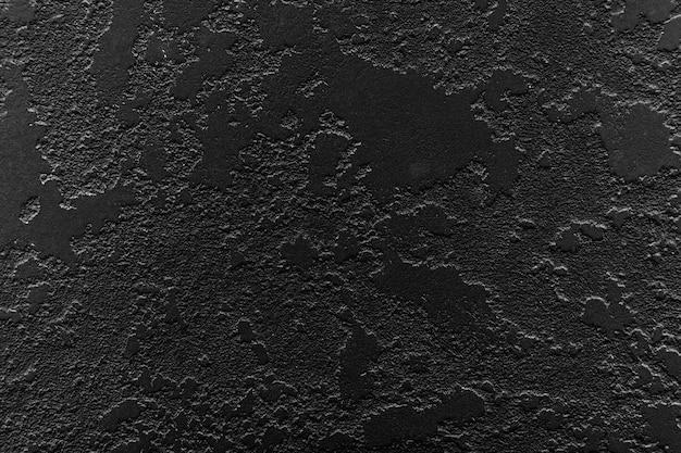 Czarny streszczenie tekstura tło z plamami tynku i odpryskami. teksturowana szara, stara odrapana powierzchnia. piękne streszczenie grunge dekoracyjne ciemne tło ściany stiuk.