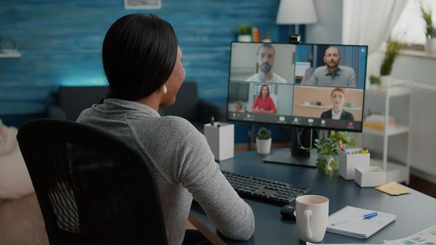 Czarny student omawia akademickie pomysły marketingowe z zespołem uczelni podczas wirtualnego spotkania telekonferencyjnego siedząc przy biurku w salonie