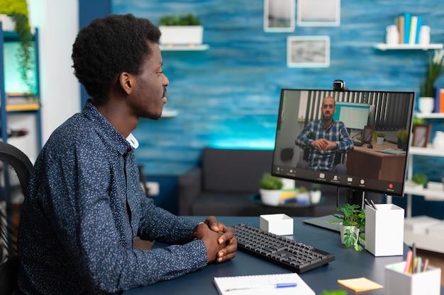 Czarny student omawiający strategię marketingową ze zdalnym nauczycielem akademickim