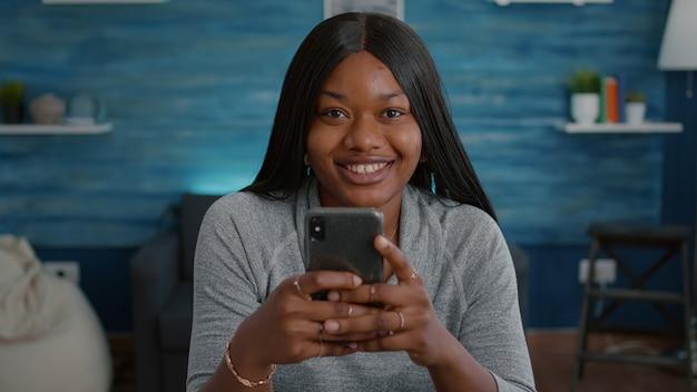 Czarny student patrzący w kamerę podczas przeglądania mediów społecznościowych, piszący wiadomość