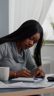 Czarny student piszący pomysły edukacyjne na karteczkach samoprzylepnych siedzący przy biurku w salonie
