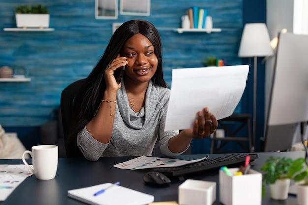 Czarny student rozmawiający z kolegą przez telefon analizujący papierkową dokumentację uniwersytecką z kursem akademickim