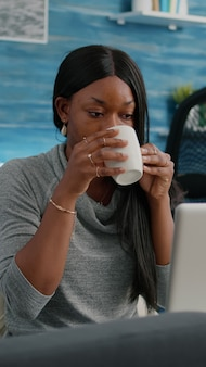 Czarny student uśmiecha się podczas pracy w artykule na blogu w mediach społecznościowych, wpisując projekt komunikacji, siedząc w salonie. blogger kobieta pijąca kawę komponowanie e-maila rozwiązującego problem z webinaru