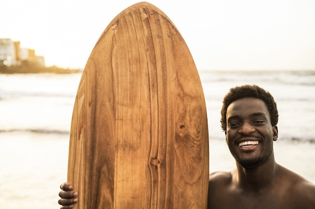 Czarny surfer trzyma deskę surfingową na plaży o zachodzie słońca - skup się na twarzy