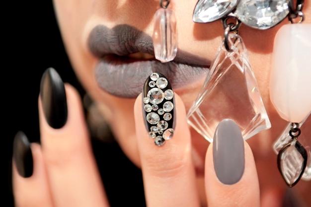 Czarny szary glam matowy makijaż i manicure z kryształkami i dekoracją na zbliżenie twarzy dziewczyny.