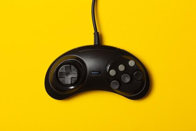 Czarny sześcioprzyciskowy gamepad na żółtym tle