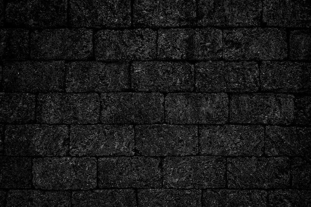 Czarny szorstki ceglany mur tekstura tło.