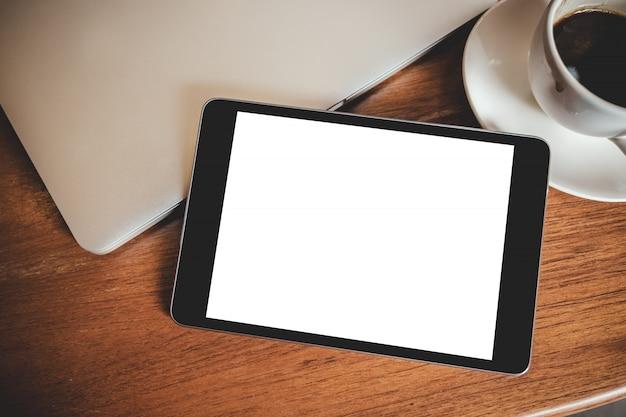 Czarny tablet pc z pustym ekranem biały pulpit z laptopem i filiżanką kawy na drewnianym stole