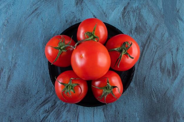 Czarny talerz czerwonych świeżych pomidorów na niebieskiej powierzchni.