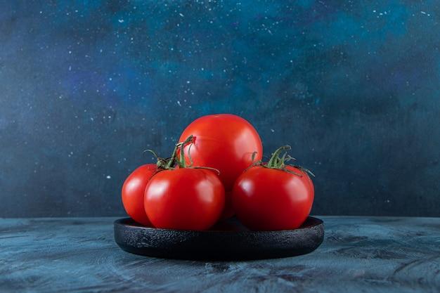 Czarny talerz czerwonych świeżych pomidorów na niebieskiej ścianie.