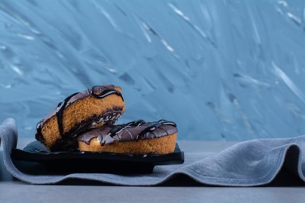 Czarny talerz dwóch świeżych słodkich ciastek czekoladowych na obrusie.