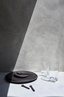 Czarny talerz i dwa szklane kubki na białym stole z padającym na nie cieniem