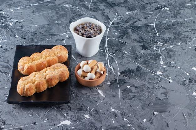 Czarny talerz kremowych ptysiów i filiżankę herbaty na marmurowym stole.