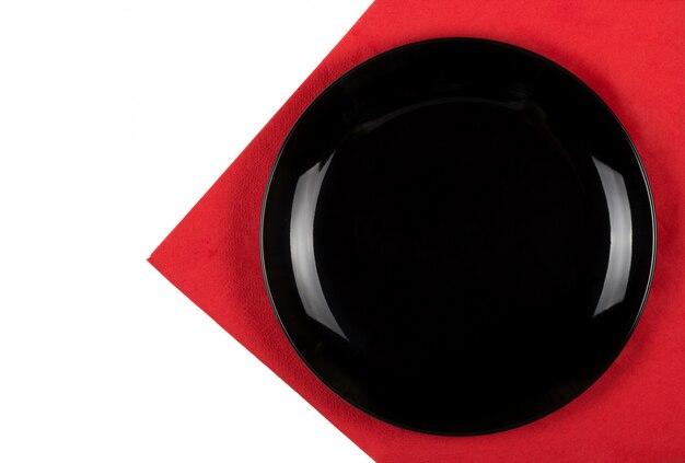 Czarny talerz na czerwonej serwetce