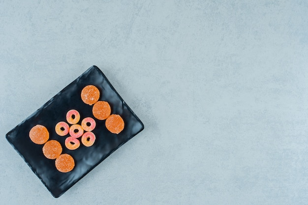 Czarny talerz pełen okrągłych pomarańczowych cukierków galaretkowych w kształcie kółek i pomarańczowych galaretek z cukrem