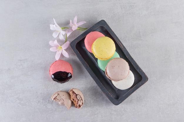 Czarny talerz pysznych słodkich makaroników z kwiatami na kamiennym stole.