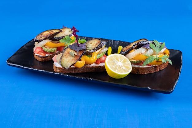 Czarny talerz pysznych tostów z warzywami na niebieskiej powierzchni