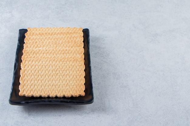 Czarny talerz smacznych herbatników umieszczony na tle kamienia.