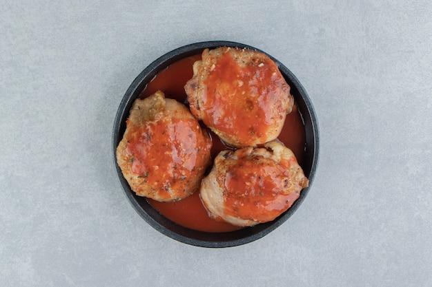 Czarny talerz smażonego mięsa w sosie pomidorowym.