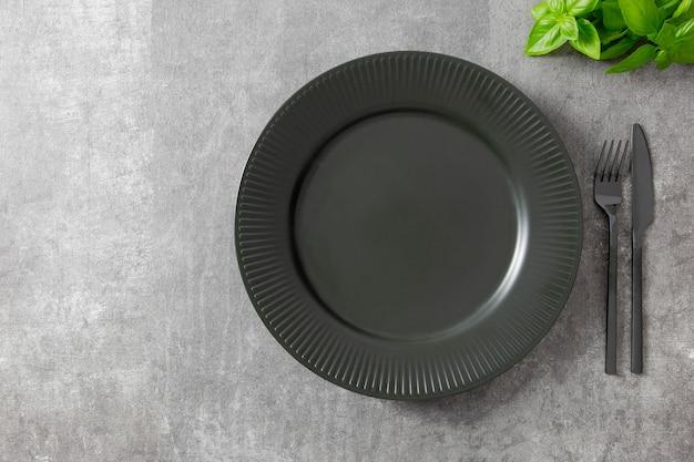 Czarny talerz, sztućce i serwetka na ciemnym tle, z ziołami.