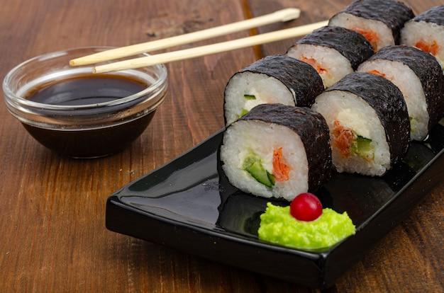 Czarny talerz z bułeczkami z łososiem na drewnianym stole zielone wasabi i sos sojowy